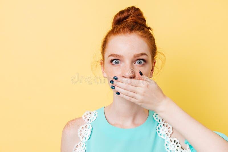 关闭盖她的嘴的惊奇的姜妇女的图片 库存图片