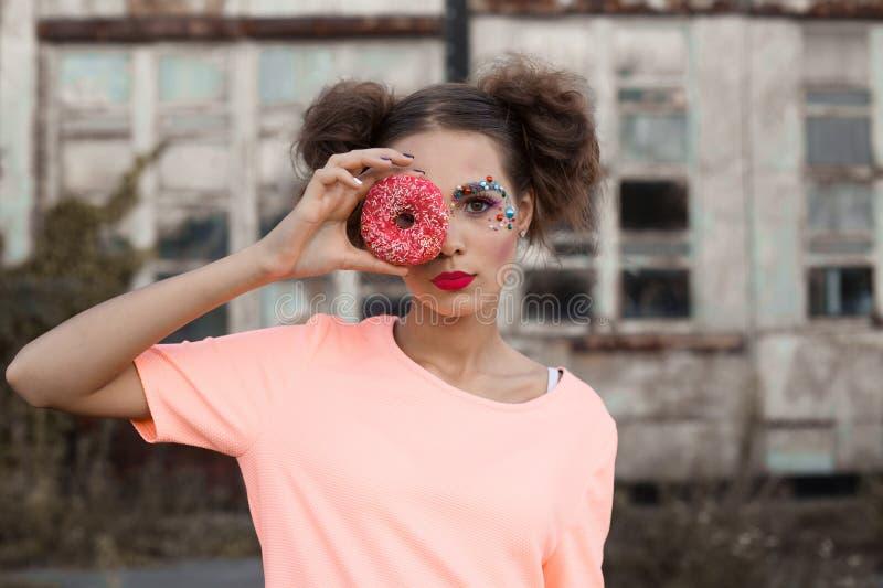 关闭盖她的眼睛的少妇画象用在白色背景的油炸圈饼 秀丽采取甜点和col的时装模特儿女孩 免版税库存照片