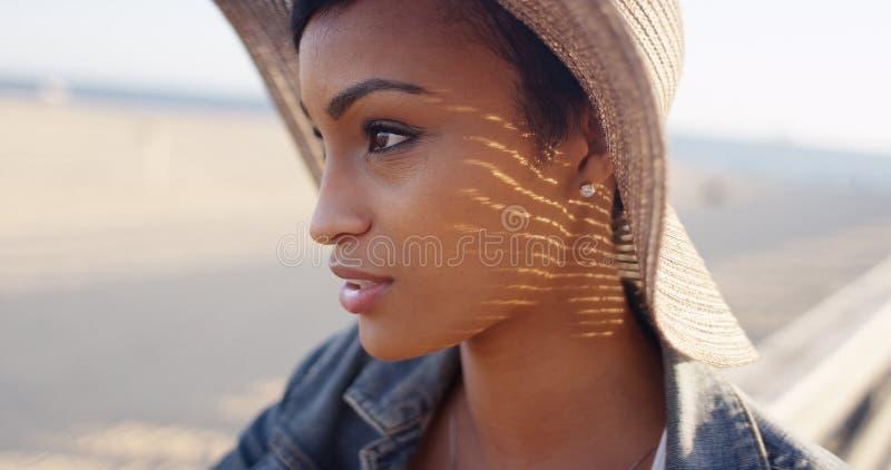 关闭相当黑人妇女射击在海滩佩带的sunhat 库存图片