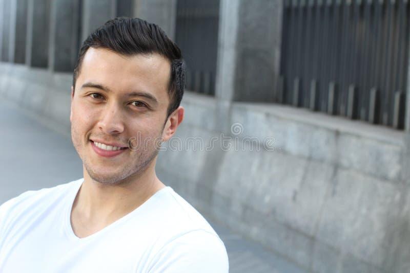 关闭看与一个快乐的微笑的表示的一个年轻西班牙少年人的画象照相机,反对都市背景 免版税库存图片