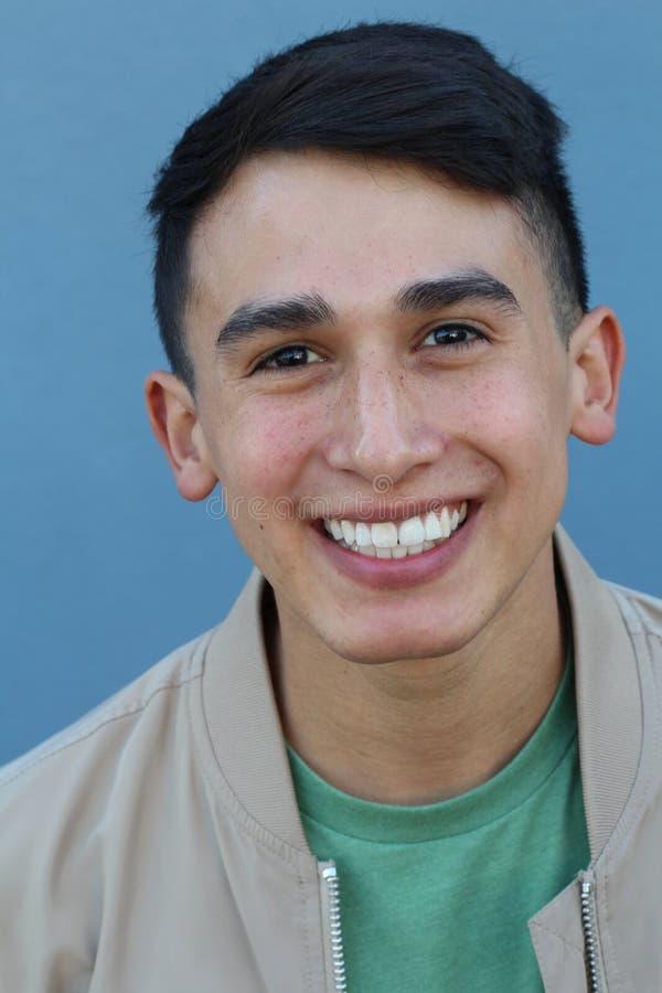 关闭看与一个快乐的微笑的表示的一个年轻西班牙少年人的画象照相机,反对蓝色背景 库存照片