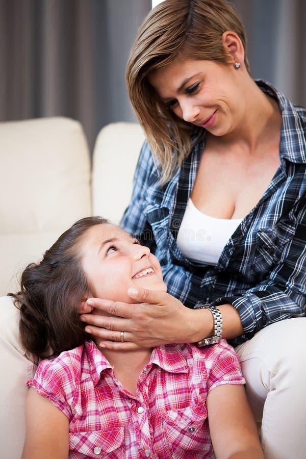 关闭看可爱她的女儿的母亲画象 免版税库存图片