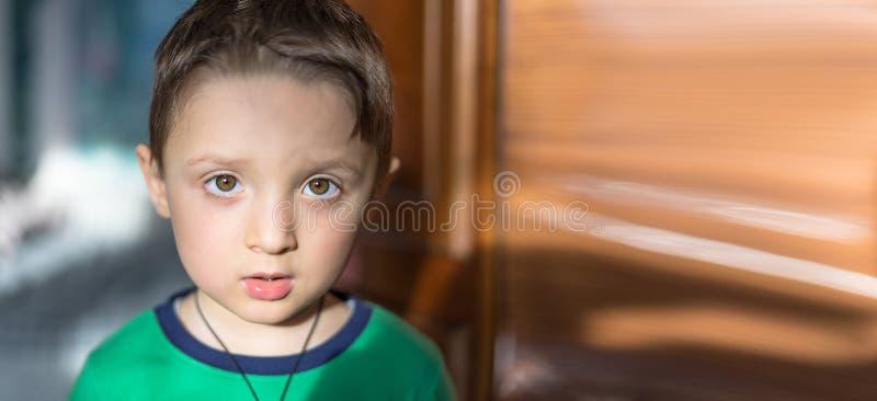 关闭看在轻的背景的一个惊奇的欧洲男婴的画象照相机 免版税库存图片