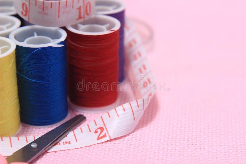 关闭看法,针,剪,穿线,裁缝米,在桃红色背景 免版税图库摄影