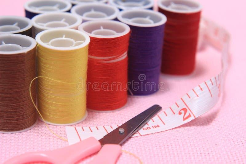关闭看法,针,剪,穿线,裁缝米,在桃红色背景 库存照片