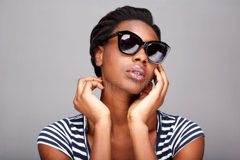 关闭看起来可爱的妇女严肃在太阳镜 免版税库存照片
