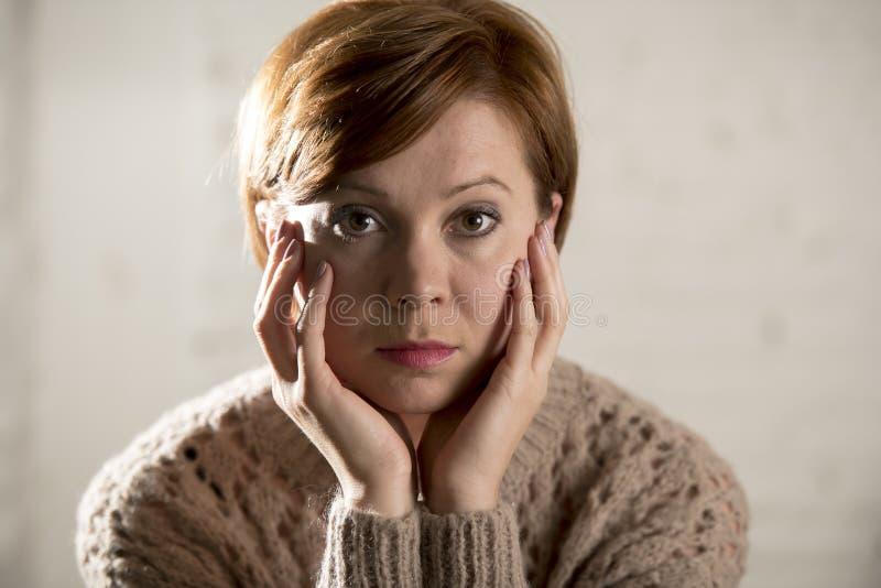 关闭看起来年轻甜和相当红色头发的妇女画象哀伤和沮丧在感到剧烈的面孔的表示偏僻 免版税库存照片