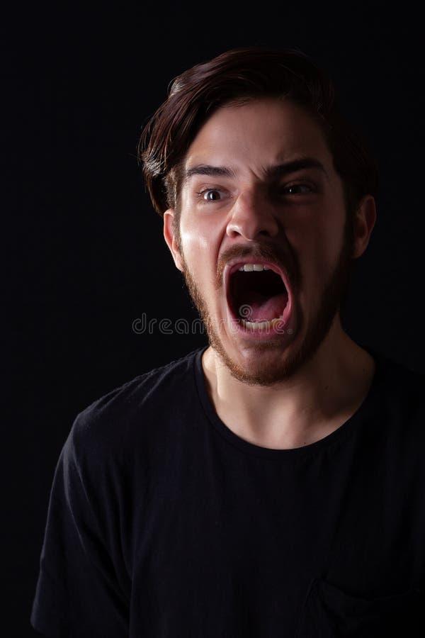 关闭看起来年轻的成年男性离开叫喊 剧烈的作用的深刻的颜色口气,黑暗和喜怒无常 免版税库存照片