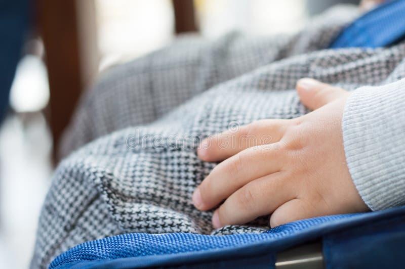 关闭睡觉在婴儿推车的婴孩手 免版税库存照片