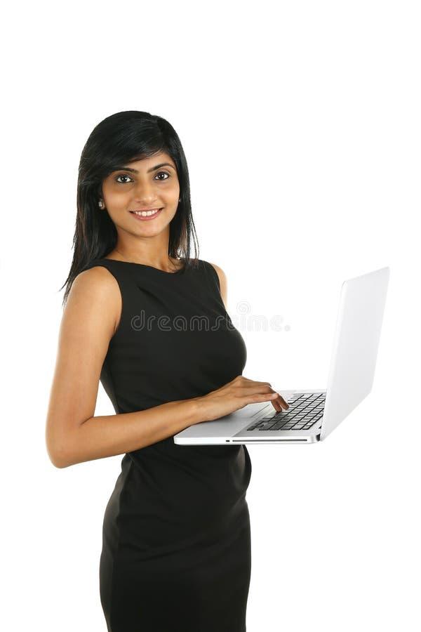 关闭研究膝上型计算机的一个微笑的印地安女商人的画象 免版税库存照片