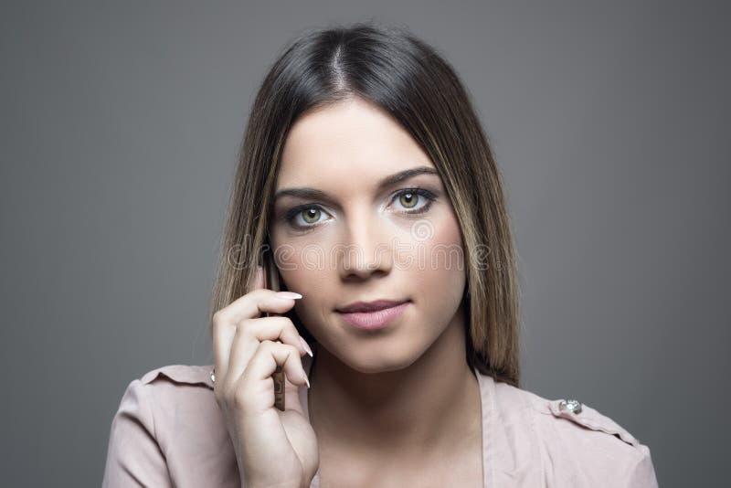关闭确信的严肃的妇女画象谈话在手机 库存照片