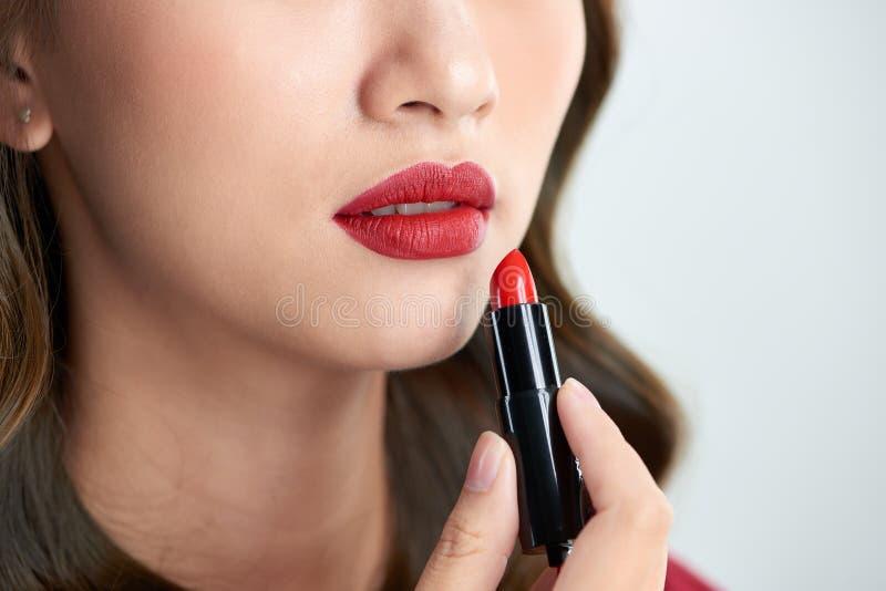 关闭秀丽skincare妇女在白色背景的作为唇膏 库存图片