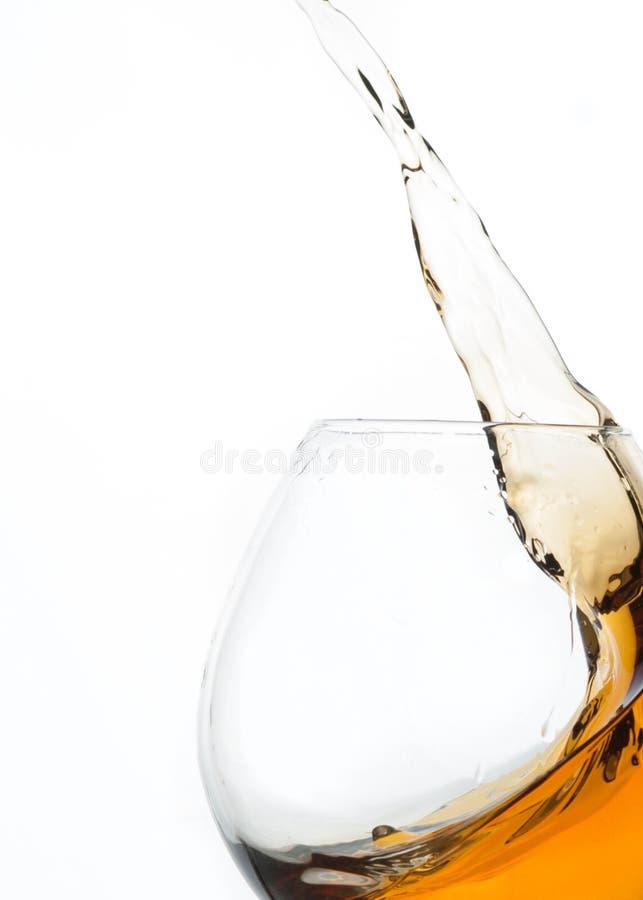 关闭科涅克白兰地飞溅在玻璃的 库存图片