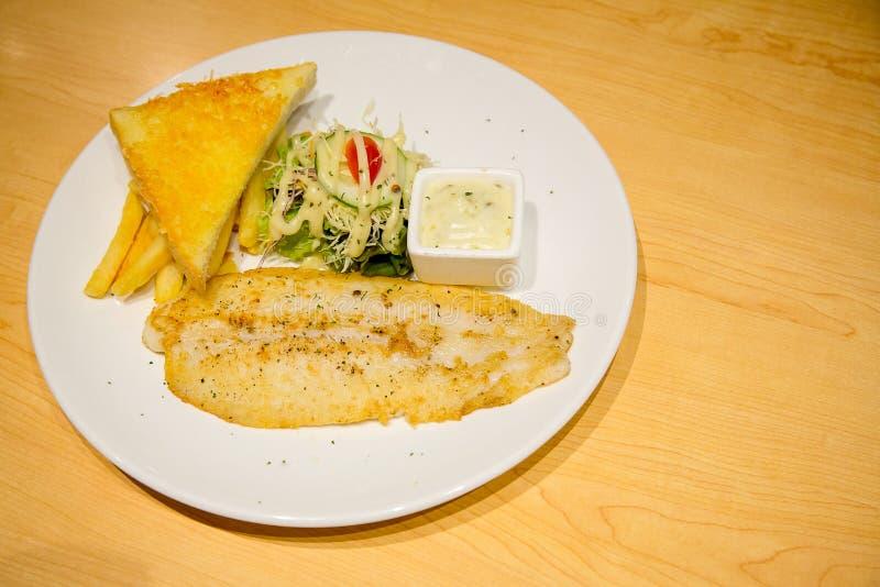 关闭移动式摄影车鱼烤牛排、蒜味面包、沙拉和柠檬白汁在集合 免版税库存照片