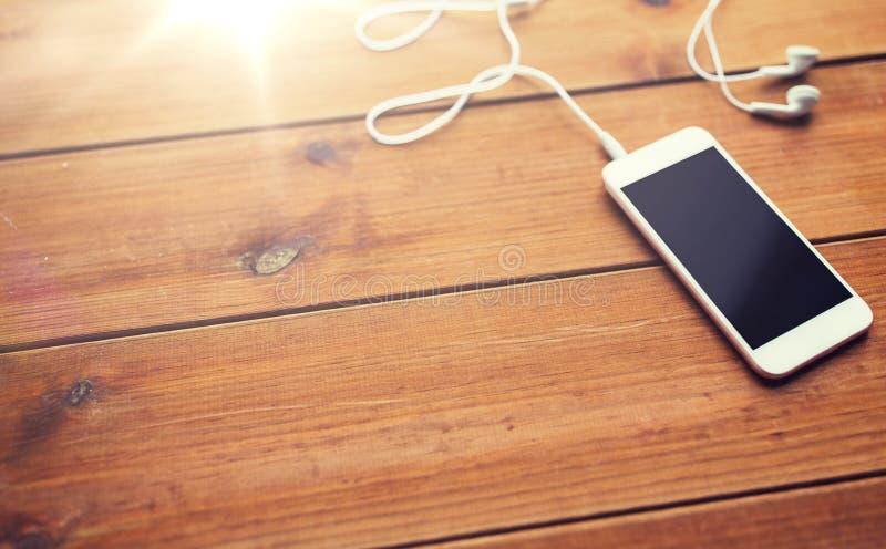 关闭空白的智能手机和耳机在木头 免版税图库摄影
