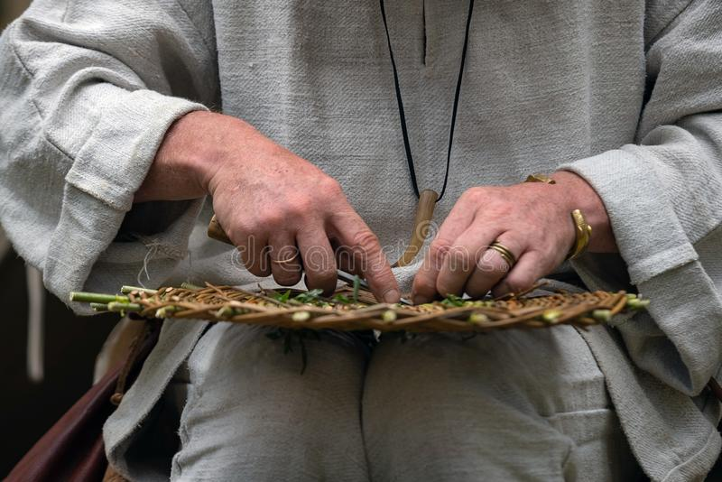 关闭穿农村衣裳的工匠做柳条筐枝杈 在乡村的传统手工制造编织的技术 图库摄影