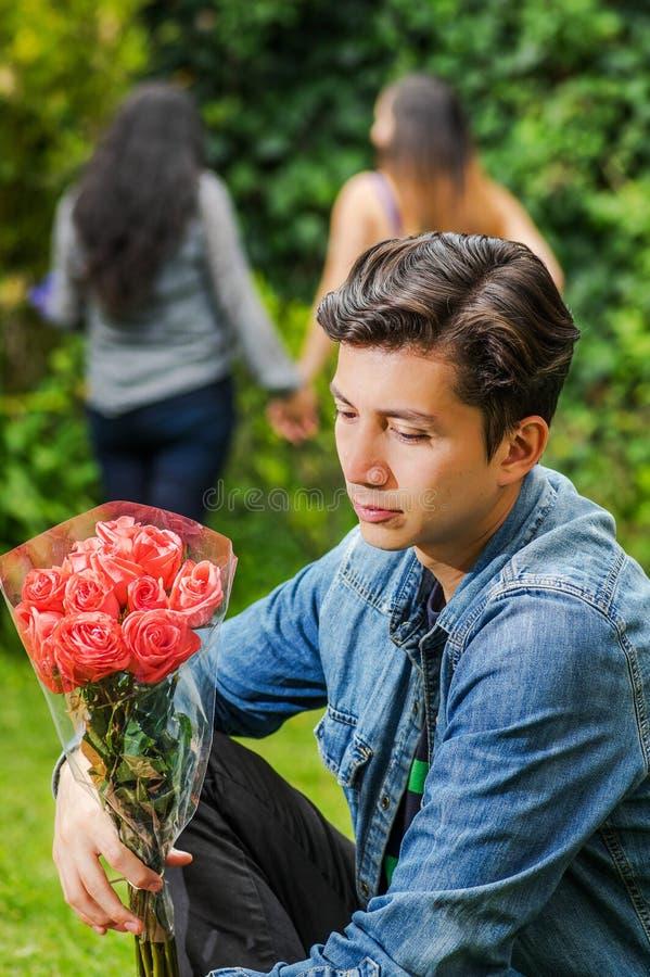 关闭穿斜纹布夹克和黑裤子的哀伤的人坐在地面举行的花在他的手上,有a的 免版税库存图片