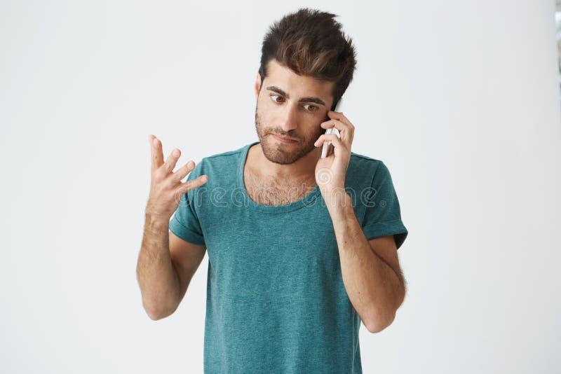 关闭穿蓝色T恤杉的不快乐的成熟白种人人,小便在电话的论据期间有他的母亲的 免版税库存图片