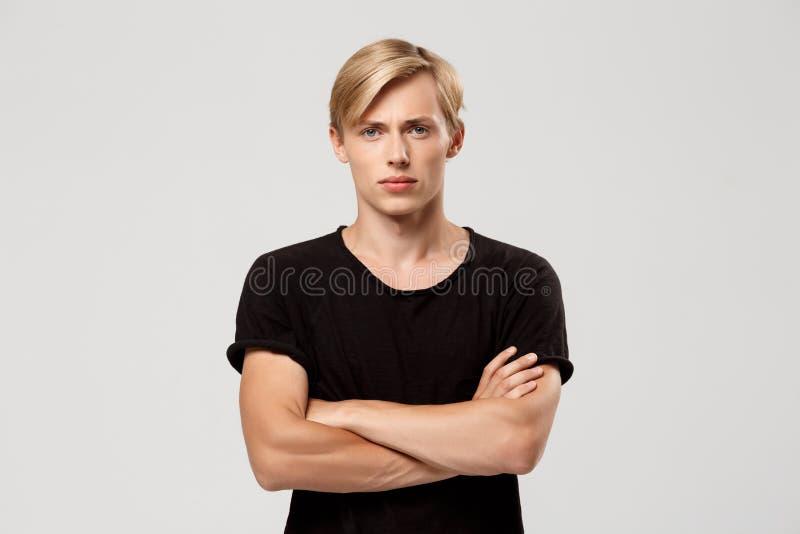 关闭穿黑T恤杉用手的确信的白肤金发的英俊的年轻人画象横渡在看的胸口  免版税库存图片