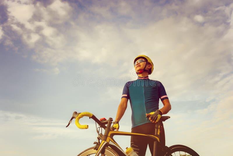关闭站立与路自行车的骑自行车者男性在日落, 免版税库存照片