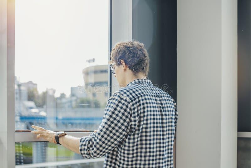 关闭站立在大窗口旁边的年轻人在地铁车站 免版税库存图片