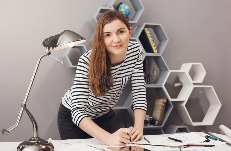 关闭站立近的桌的年轻迷人的快乐的工程师学生女孩画象,握在工作证明书的手 免版税图库摄影