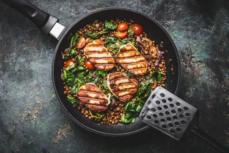关闭素食食物概念 健康扁豆膳食用菠菜和油煎的乳酪在烹调平底锅在土气背景与  库存照片