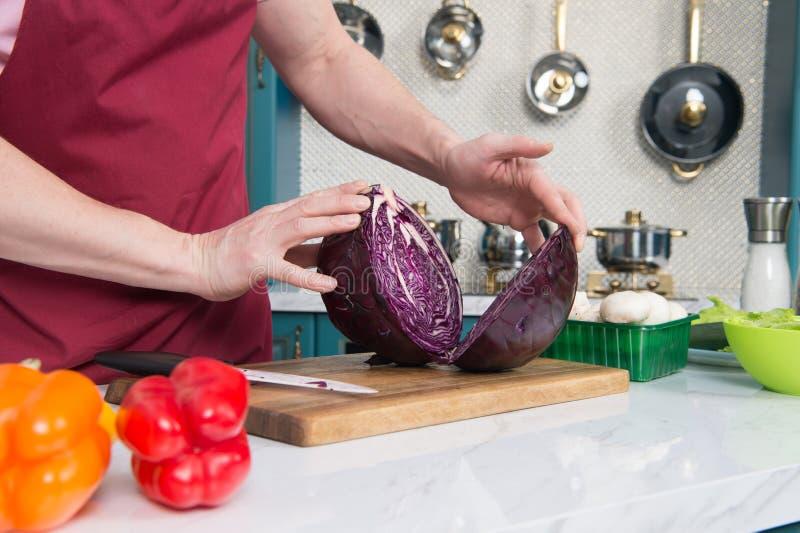 关闭红叶卷心菜的两部分在桌上的 烹调红叶卷心菜的两部分举行  圆白菜的两部分特写镜头  免版税库存照片