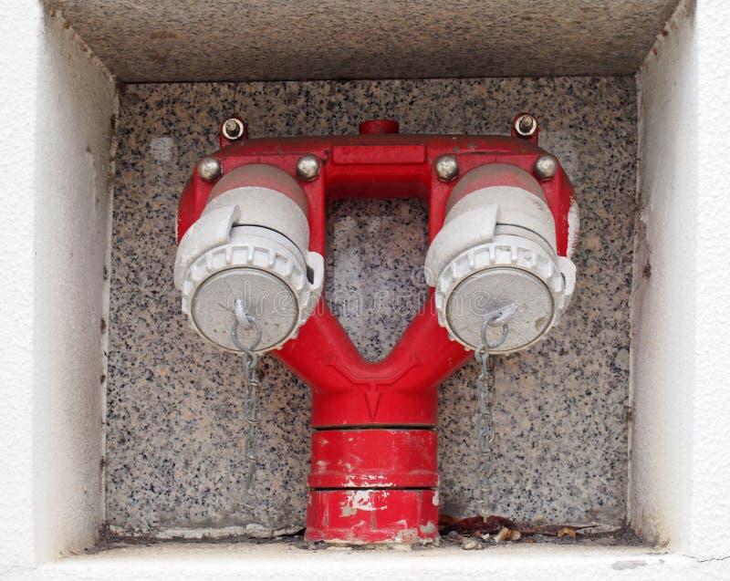 关闭红色双重紧急室外消防龙头插页入大厦的墙壁 库存图片