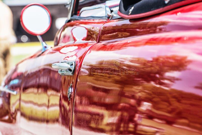 关闭红色经验丰富的汽车照片有后视镜和手的 免版税库存照片