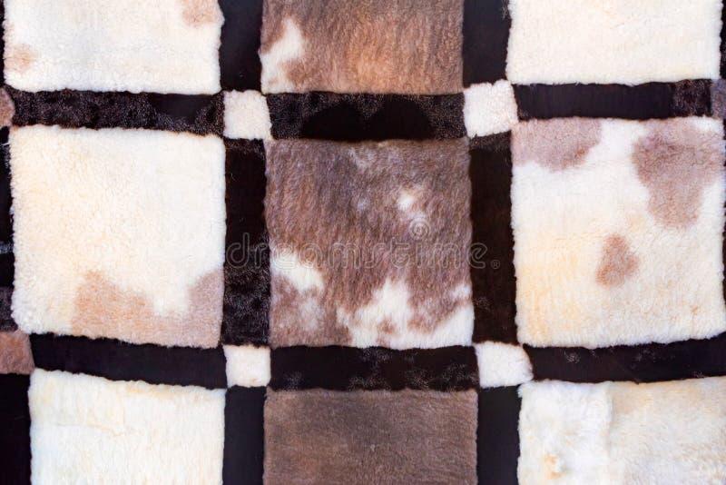 关闭纹理毛皮地毯做了黑,灰色和白色零件 库存照片