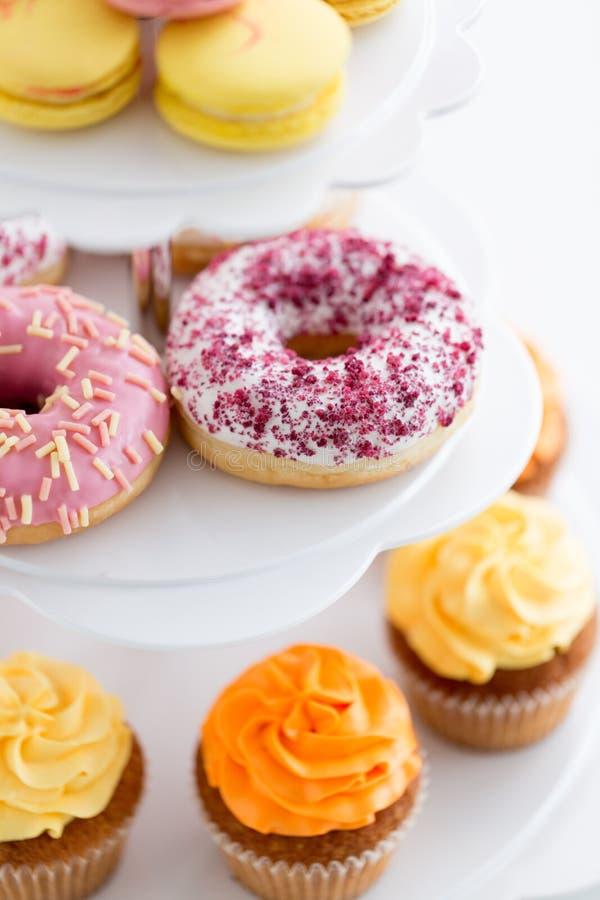 关闭给上釉的油炸圈饼和杯形蛋糕在立场 图库摄影