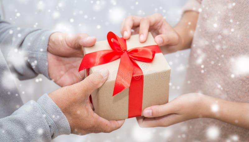 关闭给礼物盒有雪背景的资深老人和他的女儿的手 库存图片