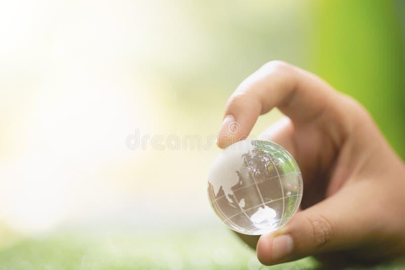 关闭绿色行星在您的手上 保存地球 库存照片