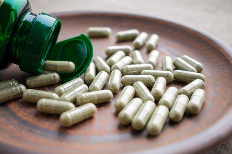 关闭绿茶萃取物胶囊并且装瓶在黏土褐色p 库存照片
