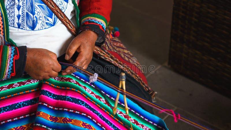 关闭编织在秘鲁 cusco秘鲁 在五颜六色的传统当地秘鲁结束打扮的妇女编织一张地毯与 库存照片