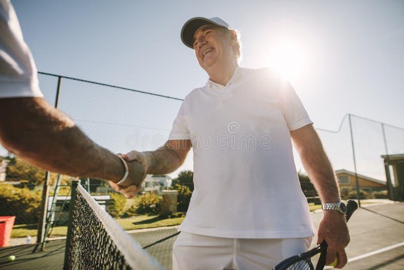 关闭网球场的一名老人 免版税库存图片