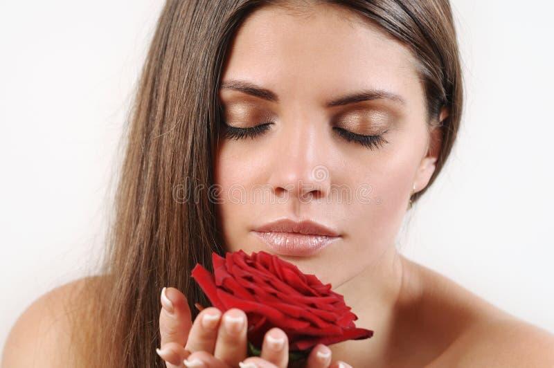 关闭美丽的妇女嗅到的红色玫瑰画象  免版税库存图片