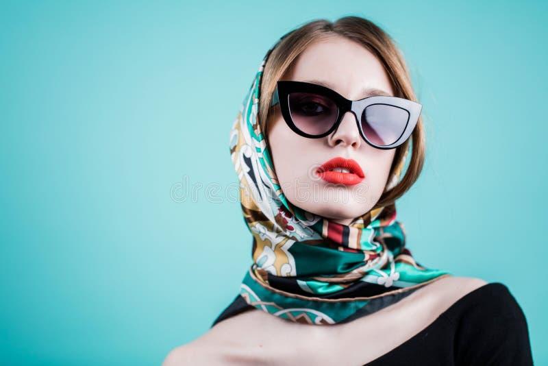 关闭美丽的妇女画象太阳镜和围巾的在蓝色背景 有看照相机的明亮的红色嘴唇的女孩 免版税库存照片