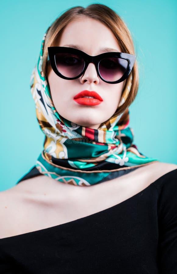关闭美丽的妇女画象太阳镜和围巾的在蓝色背景 有看照相机的明亮的红色嘴唇的女孩 图库摄影