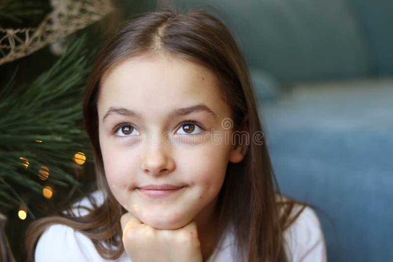 关闭美丽的小女孩画象有坐在圣诞树作白日梦的棕色眼睛的新年奇迹下 图库摄影