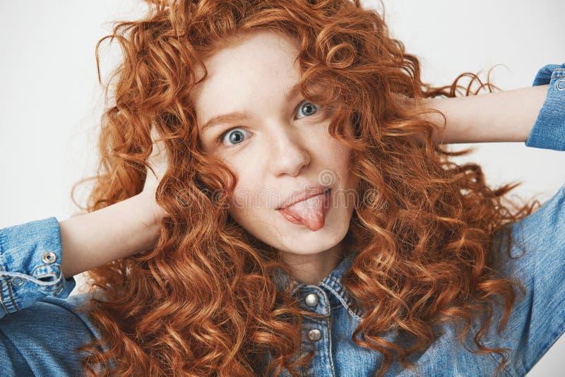 关闭美丽的微笑姜女孩感人的头发显示看照相机的舌头 奶油被装载的饼干 库存照片