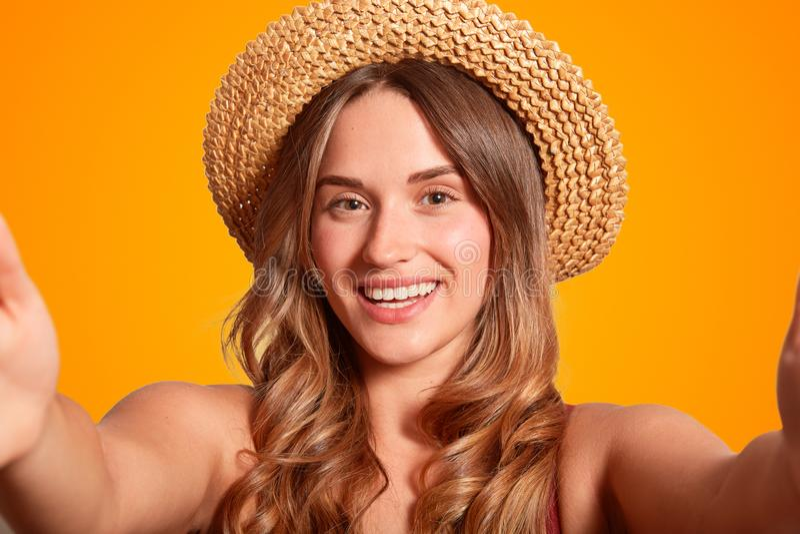 关闭美丽的微笑的女性射击有健康纯净的皮肤的,暴牙的微笑,穿典雅的草帽,做selfie画象pos 免版税库存照片