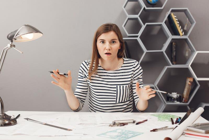 关闭美丽的滑稽的年轻欧洲女性自由职业者的在激动和震惊神色的设计师传播的手画象  库存图片