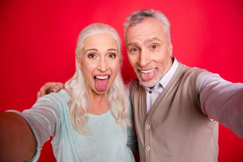 关闭美丽的照片她她他他对与夫妇合作使采取selfies滑稽质朴的他年迈的白发人夫人 图库摄影