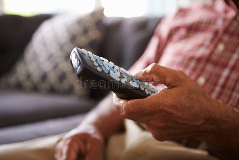 关闭老人坐拿着电视的沙发遥远 图库摄影