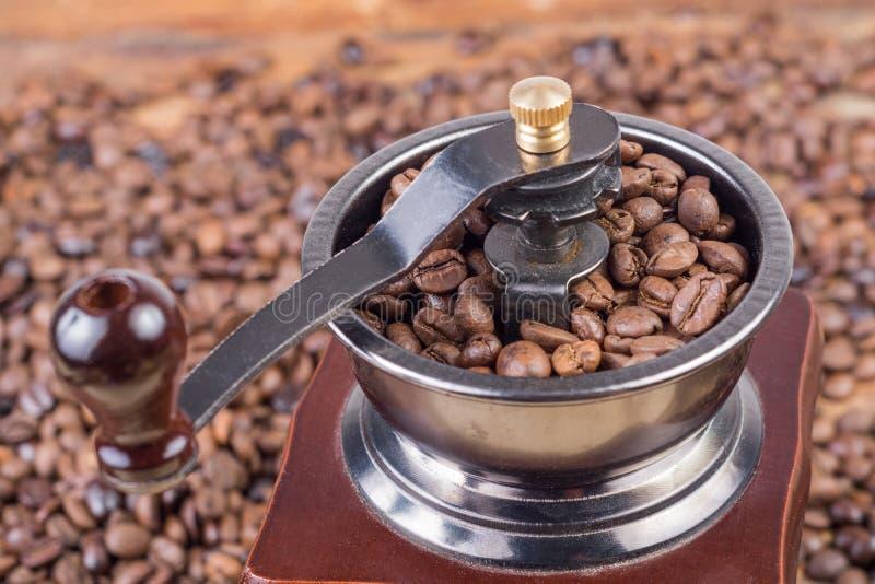 关闭老减速火箭的磨咖啡器用烤咖啡豆 免版税库存图片
