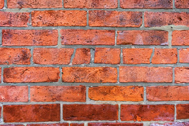 关闭老参差不齐的红砖墙壁背景 免版税库存照片