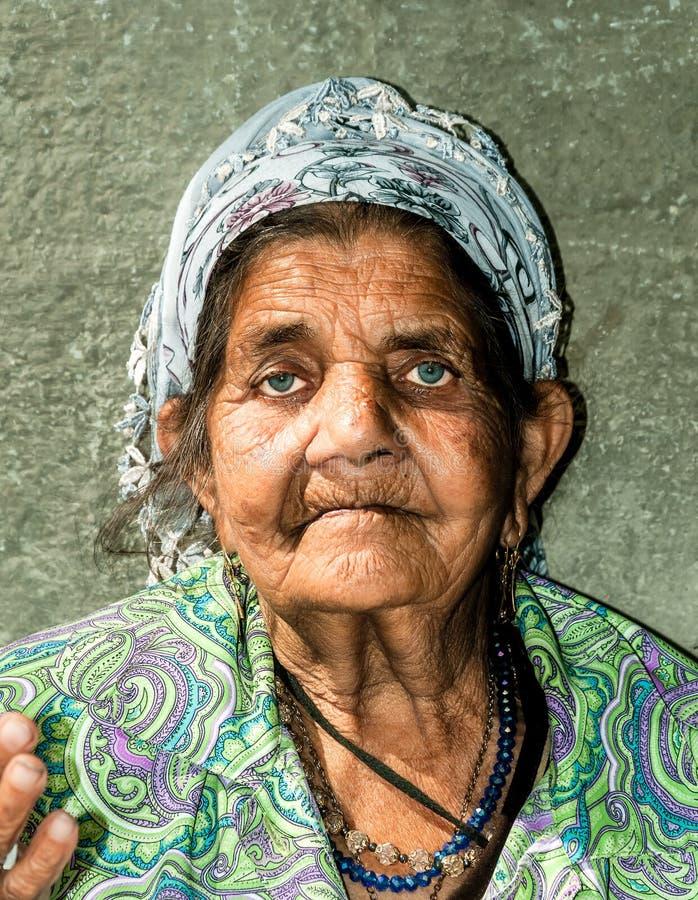 关闭老无家可归的吉普赛叫化子妇女画象有起皱纹的面孔皮肤的乞求为在街道上的金钱在城市和looki 库存图片