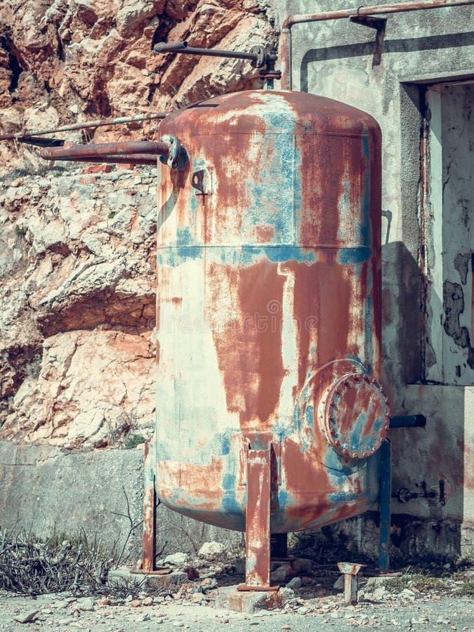 关闭老生锈的金属坦克侧视图在被放弃的industr的 免版税库存照片